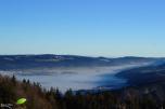 Vue depuis le haut de la falaise sur un village pris dans la brume au petit matin